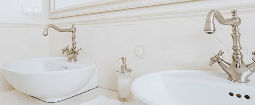 Bathroom with white ceramic sinks with vintage style faucets.