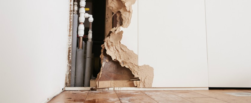 A damaged wall exposing burst pipes with water on the floor.